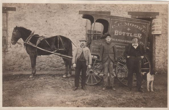"Photo taken at Chambersburg, Pa. showing Cliff Moore's beer bottling wagon. Persons in the picture, from left to right... James Draden Moore (1859-1899), unknown person, Cyrus Sanders Moore. The horse's name was ""Duke"", but the dog's name was not recorded on the photo."